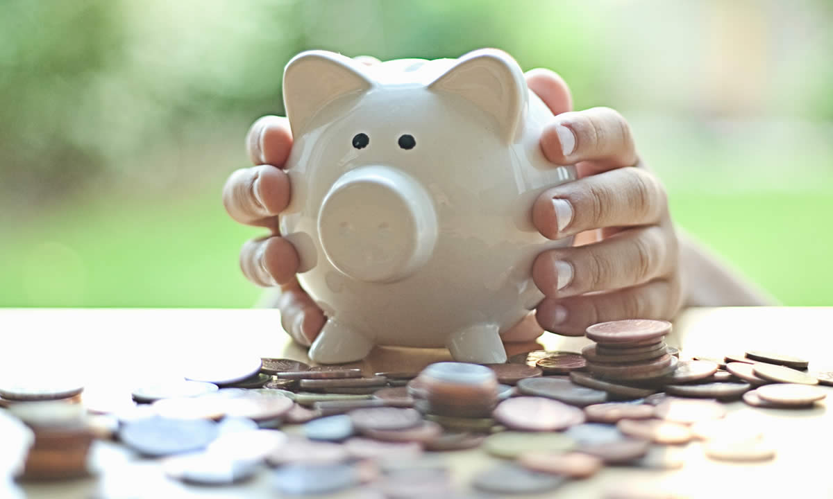 Hands holding a piggy bank and a pile of coins