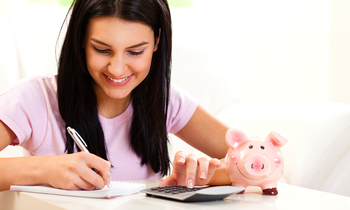 Woman writing in a notebook, with a calculator and piggy bank next to her