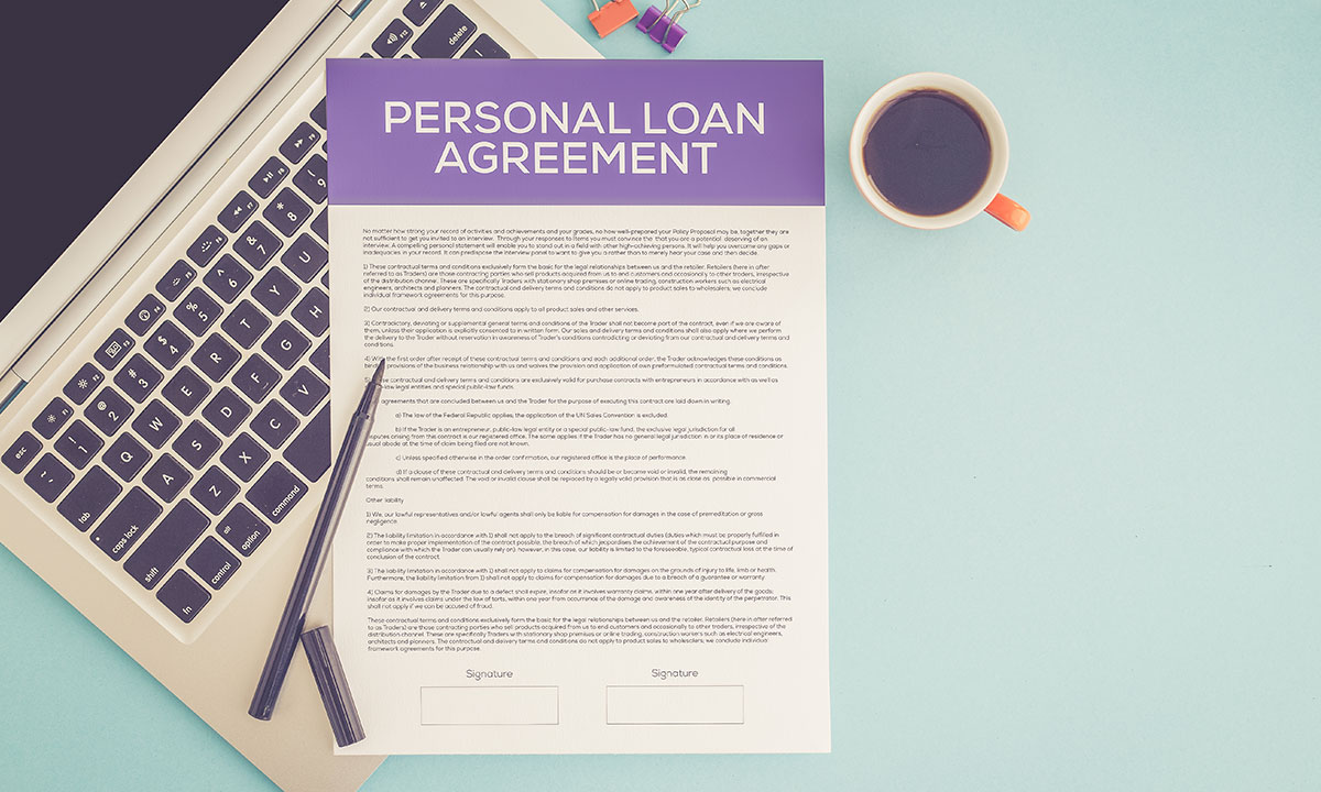 Personal loan agreement on a desk, laptop, pen and cup of coffee