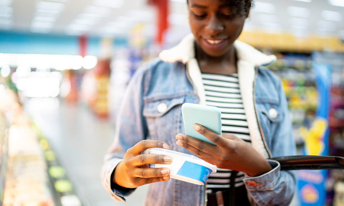 A girl holding up an item in a supermarket and scanning the barcode on her phone