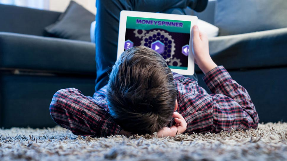 Boy looking at MoneySense on an iPad as he lies on floor at home